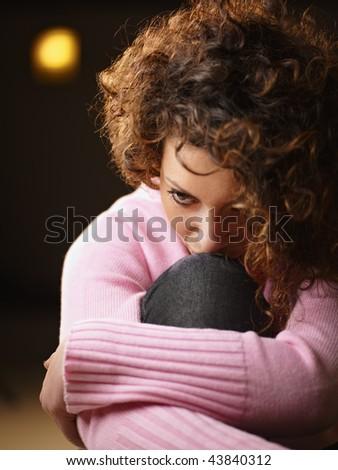 sad woman with legs drawn, looking away - stock photo