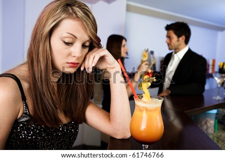Sad women and happy couple in the background. Focus on the women - stock photo