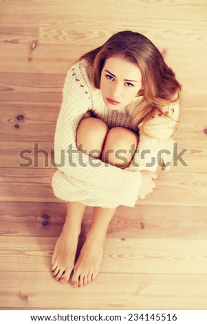 Sad, worried beautiful caucasian woman sitting in sweater. Indoor background. - stock photo