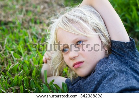 Sad, worried child alone lying on grass in park