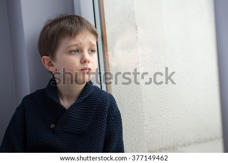 Sad 7 years boy child looking out the window. Rainy day - stock photo