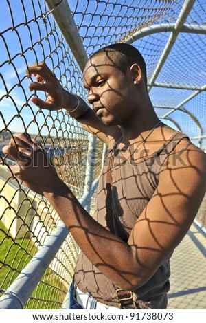 Sad young African American man gripping a chain link fence. - stock photo