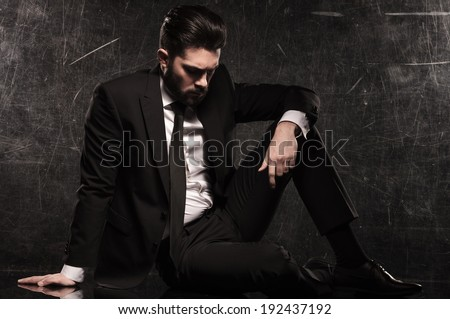 sad young bearded business man looking down while resting on the floor - stock photo