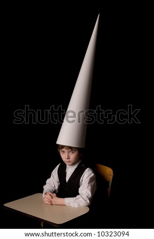 Sad young boy in a dunce cap at a school desk over a black background - stock photo