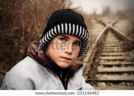 Sad young boy sitting on abandoned place - stock photo