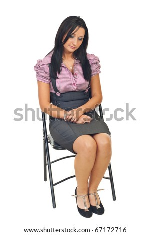 Sad young corporate woman sitting on chair and looking down isolated on white background