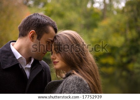 sad young couple in autumn park together