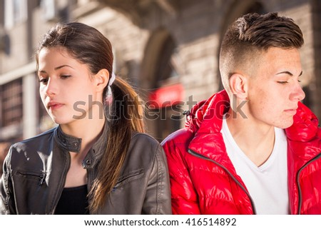 Sad young couple sitting on the bench in urban area - stock photo
