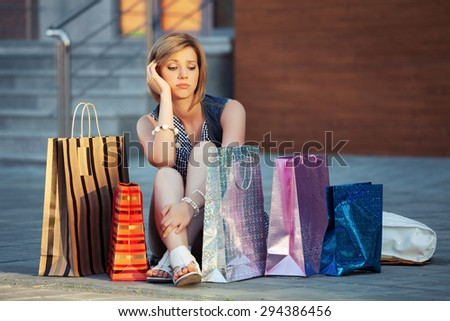 Sad young fashion woman with shopping bags sitting on a sidewalk - stock photo