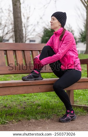 Sad young female athlete sitting on a bench on a cold winter day in the track of an urban park. - stock photo