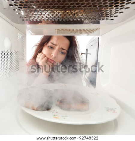 Sad young girl burn toasts in a microwave