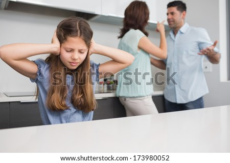 Sad young girl covering ears while parents quarreling in the kitchen at home - stock photo
