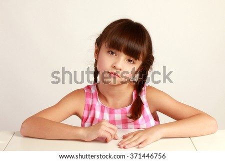 sad young girl poses for a picture isolated on white - stock photo