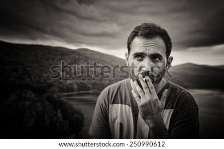 Sad young handsome man smoking cigarette in the autumn park. Sepia picture. - stock photo