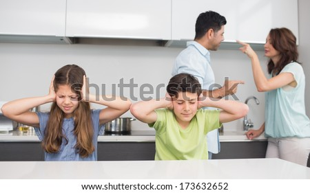 Sad young kids while parents quarreling in the kitchen at home - stock photo