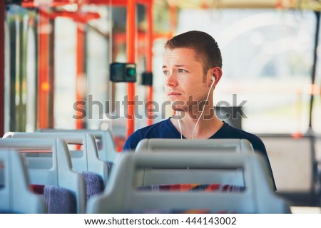 Sad young man is traveling by tram (bus). Everyday life and commuting to work by public transportation. Man is wearing headphones and listening to music. - stock photo