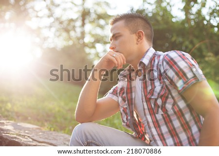 Sad young man looking down in outdoor - stock photo