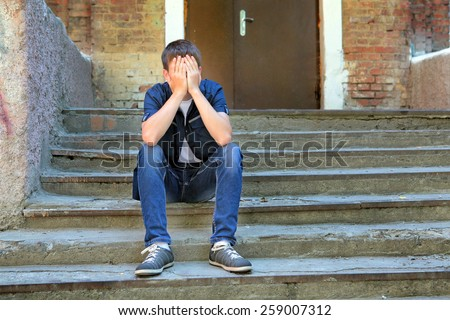 Sad Young Man on the landing Steps of the Old House - stock photo