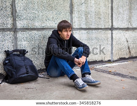Sad Young Man sit by the Wall on the Street