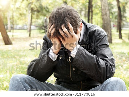 Sad Young Man sit in the Autumn Park - stock photo