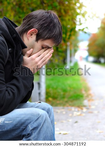 Sad Young Man sit on the Bench at the City Street - stock photo