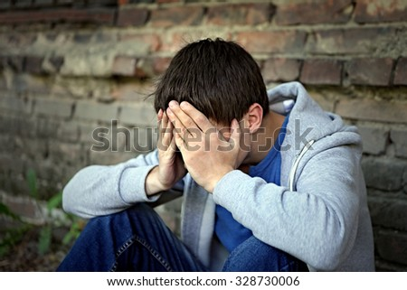 Sad Young Man sit on the Brick Wall Background