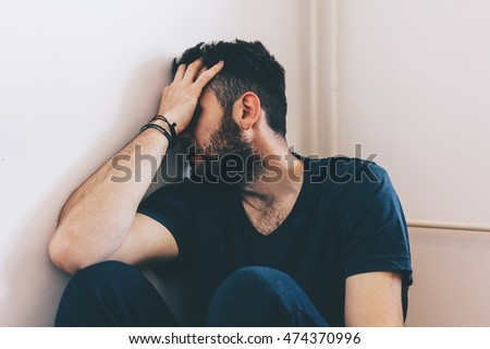 Sad young man sitting in the corner of the room