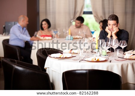 sad young man waiting date restaurant table - stock photo