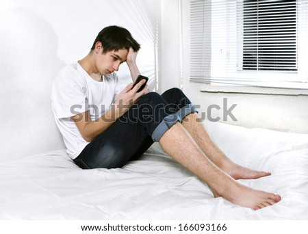 Sad Young Man with Cellphone sitting on the bed - stock photo