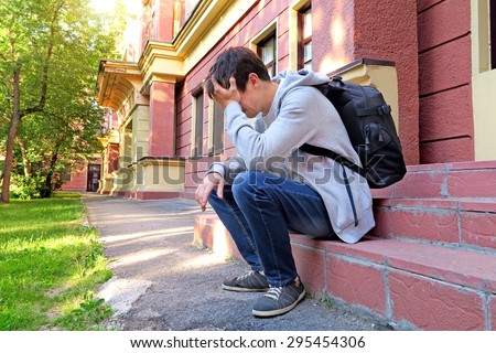 Sad Young Man with Knapsack on the Porch of the House - stock photo