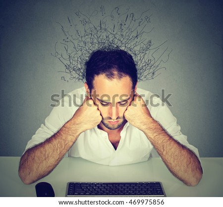 Sad young man with worried stressed face expression and brain melting into many lines question marks sitting at table looking at computer keyboard. Adhd anxiety disorders
