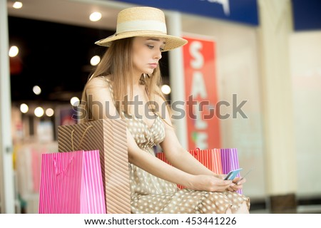 Sad young pretty woman sitting in shopping mall with shopping bag around thinking. She is holding credit cards looking upset as no money left. Buying too much on expensive shopping time concept - stock photo