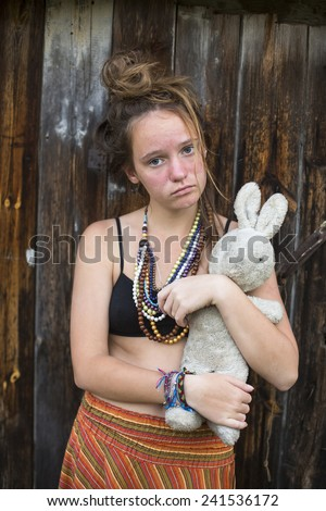 Sad young teen girl with old toy rabbit in the hands of the outdoors in rural areas. - stock photo