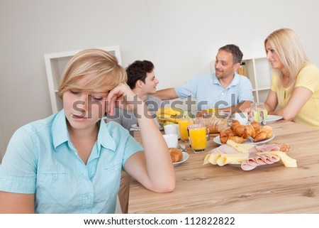 Sad young teenage girl sitting forlornly in the foreground