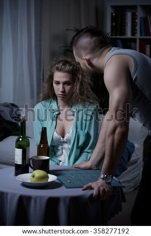 Sad young woman and her angry aggressive husband - stock photo