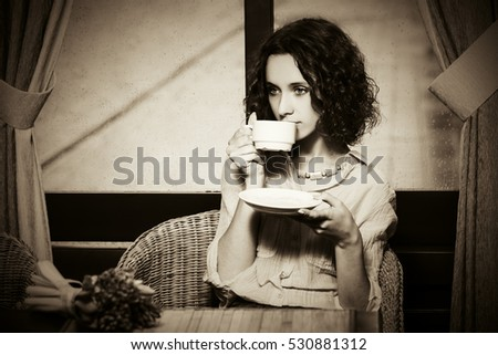 Sad young woman drinking a tea. Stylish fashion model at restaurant