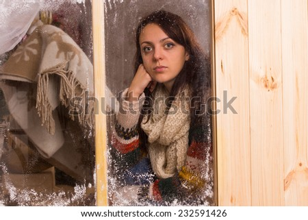 Sad young woman in a winter cabin at Christmas staring glumly through a frosted wooden window with a look of loneliness and longing - stock photo