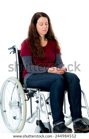 sad young woman in wheelchair in front of white background