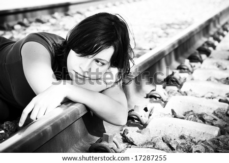 Sad young woman laying on the railway. - stock photo