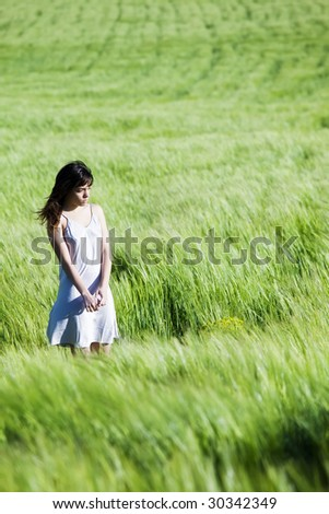 Sad young woman on green meadow. - stock photo