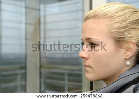 Sad young woman on window - stock photo