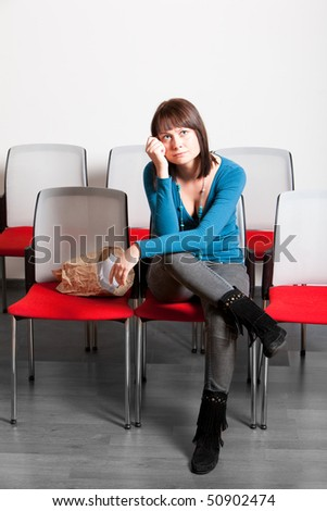 sad young woman sitting and getting emotional while watching movie, holding hand on her cheek, vertical shot - stock photo