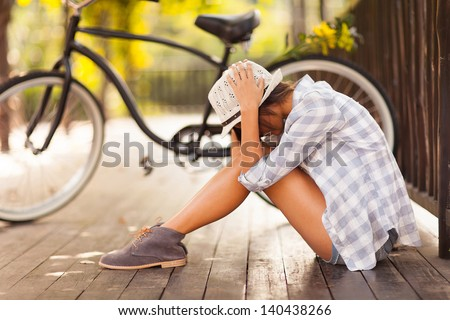sad young woman sitting at the park next to bicycle - stock photo