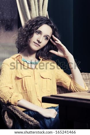 Sad young woman sitting in a chair - stock photo