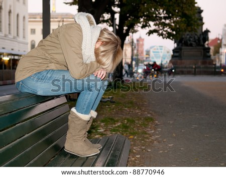 sad young woman sitting on a bench - stock photo