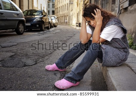 sad young woman sitting on sidewalk in city - stock photo
