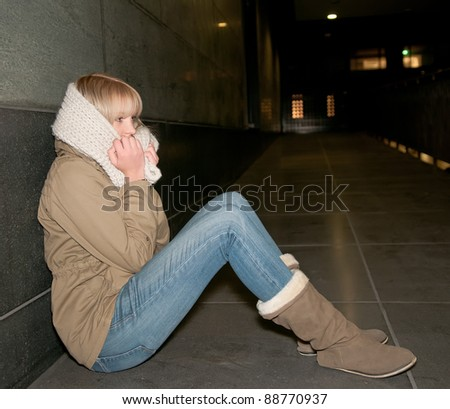 sad young woman sitting on the street - stock photo