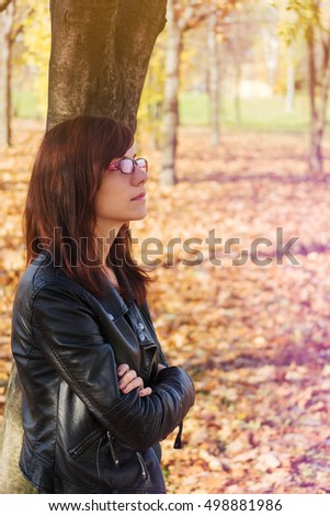 Sad young woman standing outdoors in a park, dreaming of something to happen