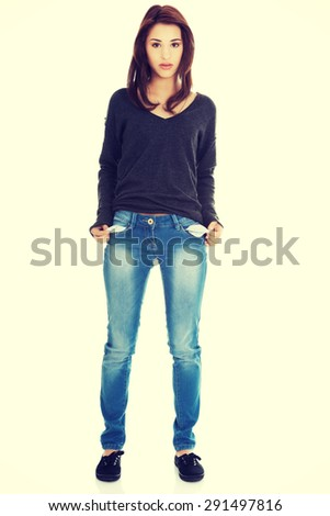Sad young woman taking out empty pockets - stock photo