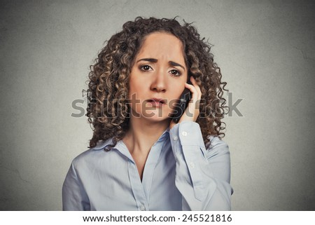 Sad young woman talking on mobile phone - stock photo